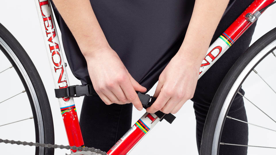 Woman installing lower front buckle of framepack on bicycle