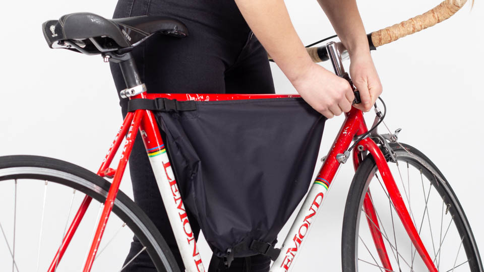 Woman installing front buckle of framepack on bicycle