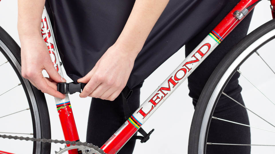 Woman installing lower rear buckle of framepack on bicycle