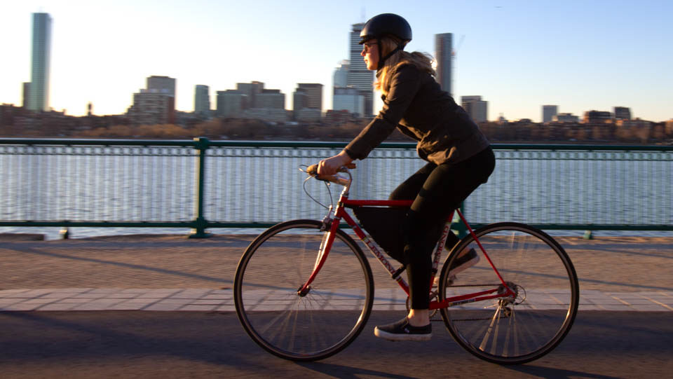 Felicity riding a 20 inch bicycle with a Framepack bike bag against Boston skyline