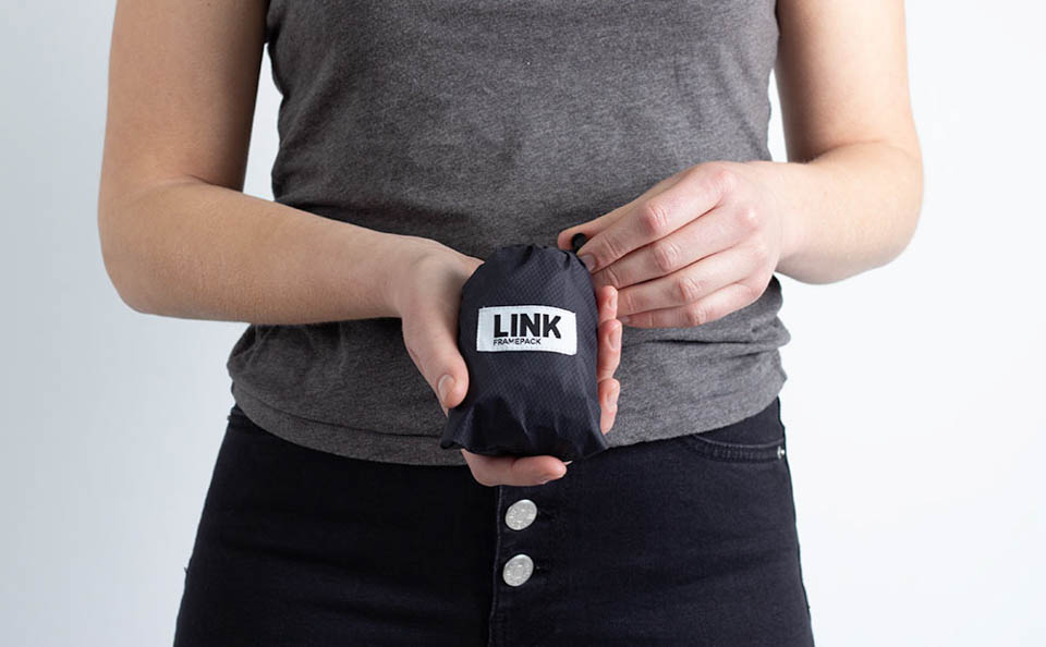 Woman holding framepack bike bag stored in its carry pouch
